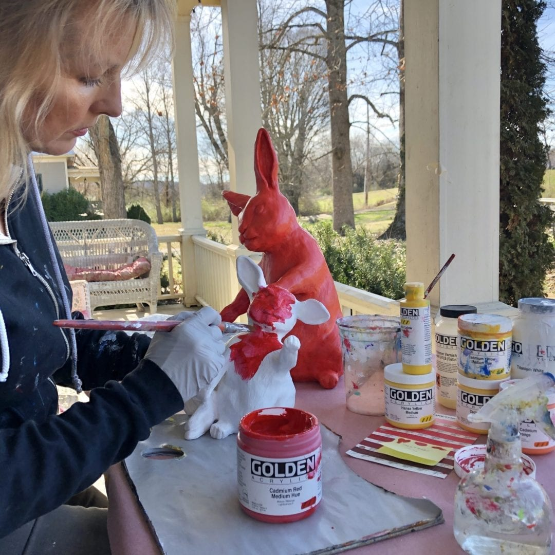 """Rachael McCampbell painting the bunnies for the Vanderbilt """"Space Bunnies"""" project. The Sculptures were placed on top of pedestals outside the elevator near the mural. © 2020 by Rachael McCampbell"""